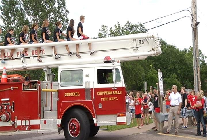 The Chippewa Falls softball team gets a ride through town on a fire truck