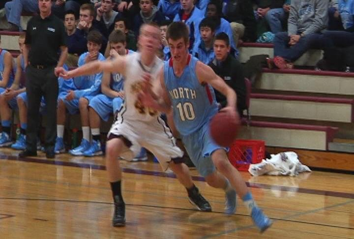 EC North's Alec Heacox drives baseline as the Huskies win at Menomonie
