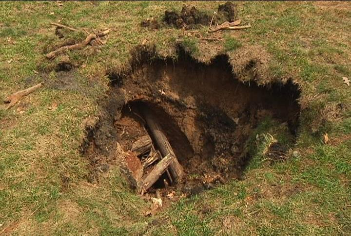 man is looking for answers afternoticing a sinkhole in his backyard